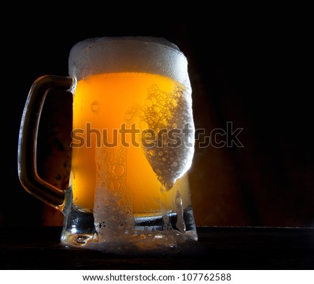 Beer in a glass with gold background - stock photo