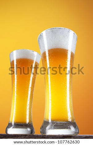 Beer in a glass with gold background
