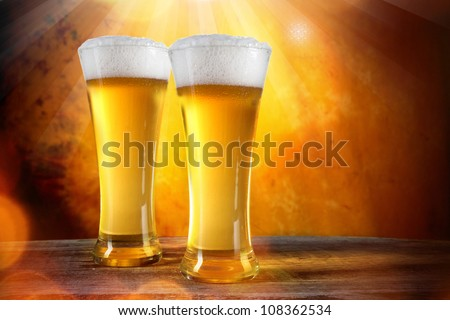 Beer in a glasses with gold background - stock photo