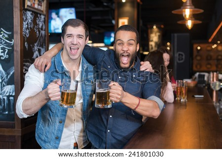 Beer in a pub is fun Portrait of two handsome friends in a pub with glasses of beer - stock photo