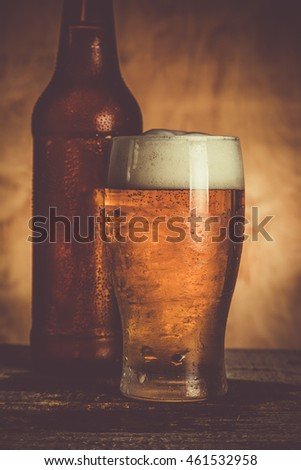 Beer in bottle and glass with ice drops