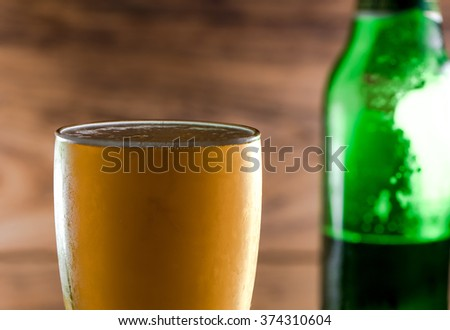 beer in glass and beer bottle on wood table - stock photo