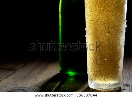 Beer in glass and bottle on a black background - stock photo