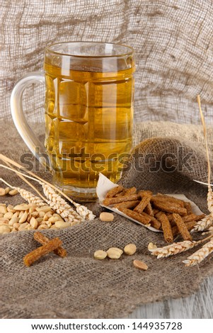 Beer in glass, crackers and nuts on bagging on wooden table