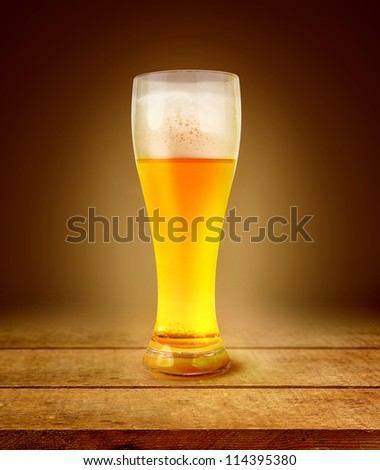 beer in glass of light on planking dark abstract background