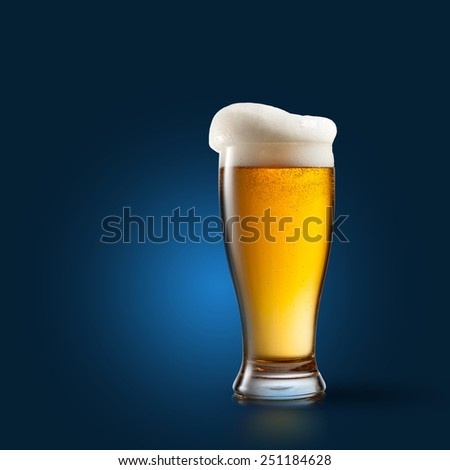 Beer in glass on blue background - stock photo
