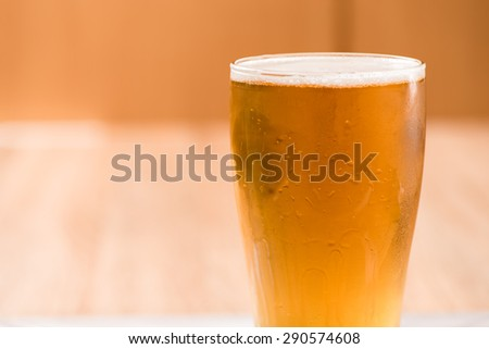 Beer in glass,on wood background - stock photo