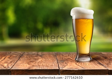 Beer in glass on wooden table with blurred city park on background, natural background with bokeh - stock photo
