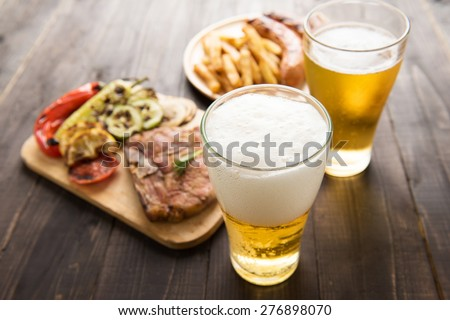 Beer in glass with gourmet steak and french fries on wooden background - stock photo