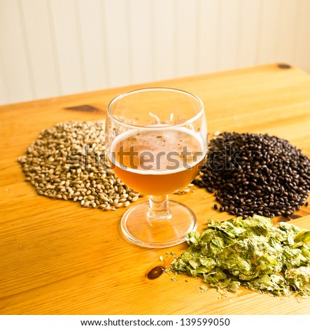 Beer in glass, with hops and malt displayed on table - stock photo