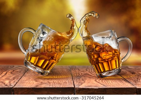 Beer in glasses and splash on wooden table with blurred autumn city park on background, natural background with bokeh - stock photo