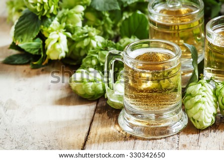 Beer in little old-fashioned mugs, and hop cones on old wooden background, selective focus
