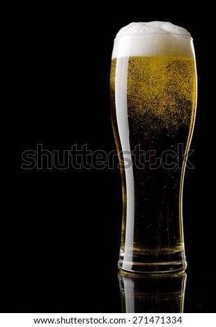 Beer into glass on black background - stock photo