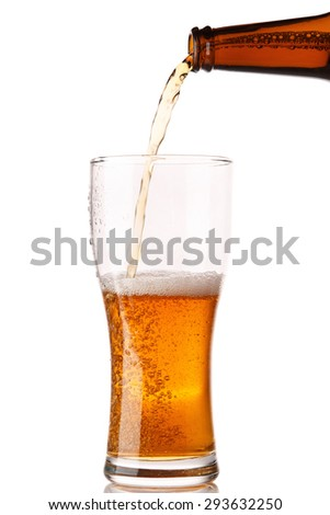 Beer is pouring into a glass over white background