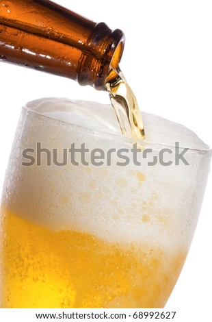 Beer is Pouring into glass on white background - stock photo