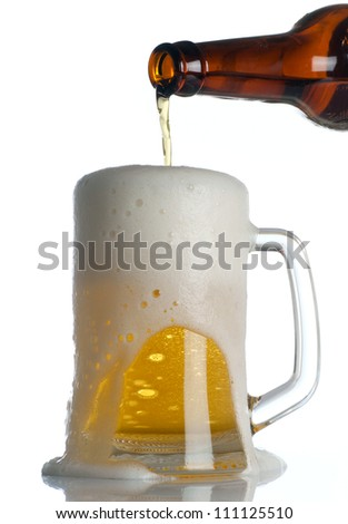 Beer is Pouring into mug on white - stock photo
