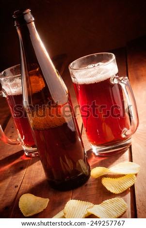 Beer mug and bottles with chips on wooden table