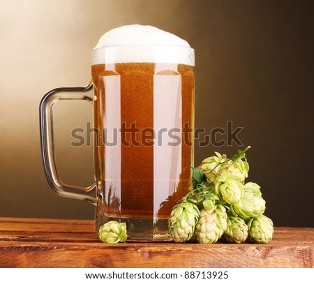beer mug and green hop on wooden table on brown background - stock photo