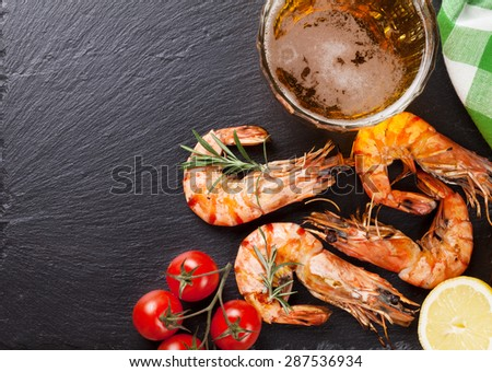 Beer mug and grilled shrimps on stone plate. Top view with copy space - stock photo