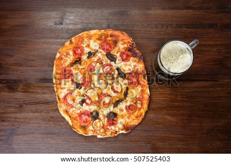 Beer mug and pizza with mozzarella on wood background. Top view