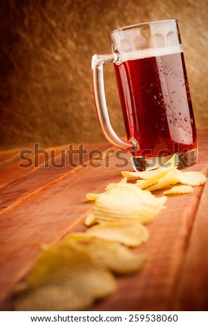 Beer mug and potatoe chips on wooden table