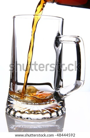 Beer mug being filled from a bottle on white background - stock photo