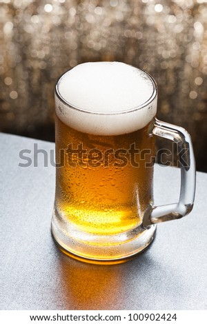Beer mug in front of a glittering background with a cool beer - stock photo