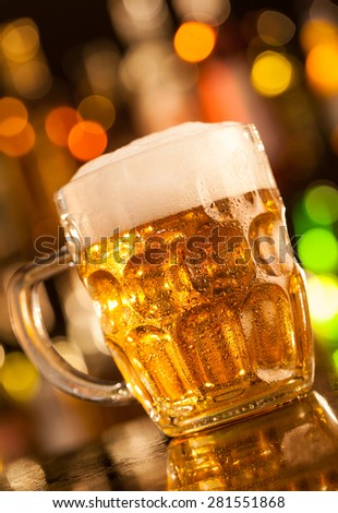 Beer mug placed on bar counter - stock photo