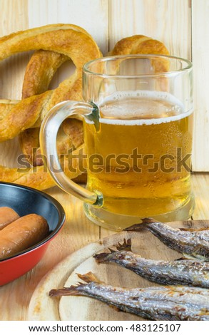 Beer mug, sausages, pretzels and grilled fishes on wooden table