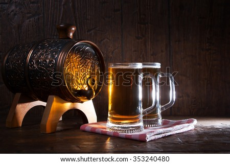 Beer mugs and barrel on a wooden background.
