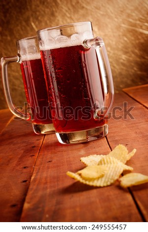Beer mugs and potatoe chips on wooden table