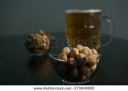 beer on the dark black wood near beer nuts - stock photo