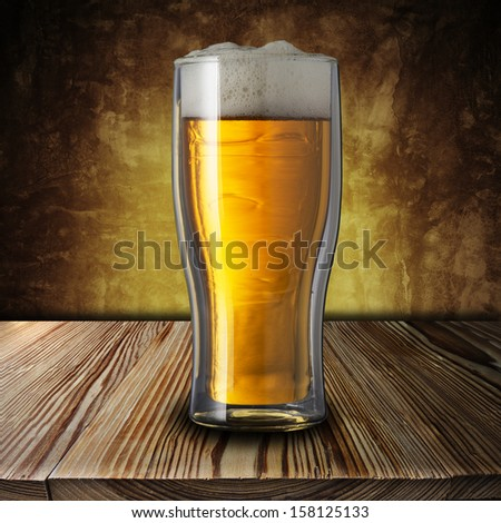 Beer on wood table with grunge background