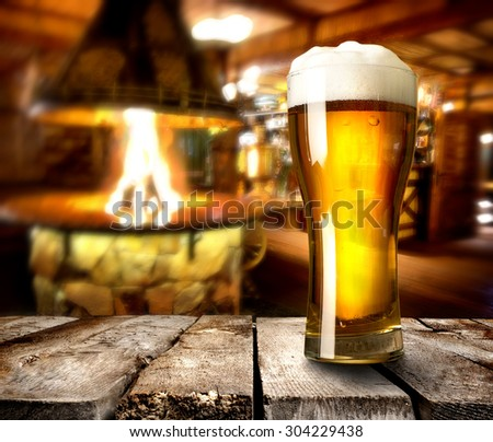 Beer on wooden table in bar with furnace - stock photo