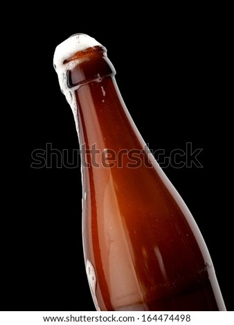 Beer overflow from a brown beer bottle, close up - stock photo