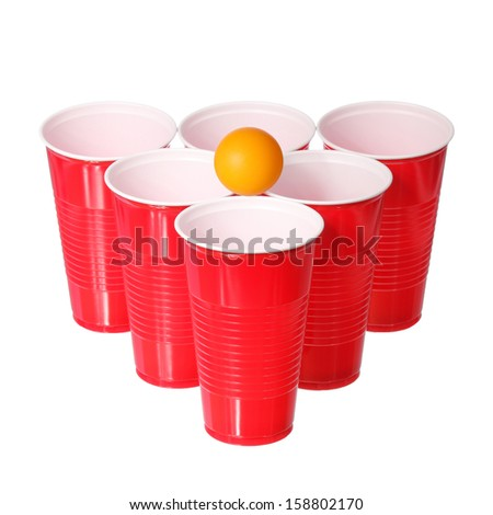 Beer pong. Red plastic cups and orange ping-pong ball isolated on white background. Closeup - stock photo