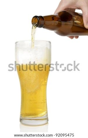 Beer pouring from bottle into glass  on white background