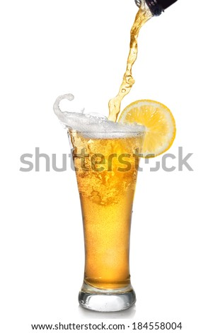 Beer pouring from bottle into glass with lemon isolated on white - stock photo