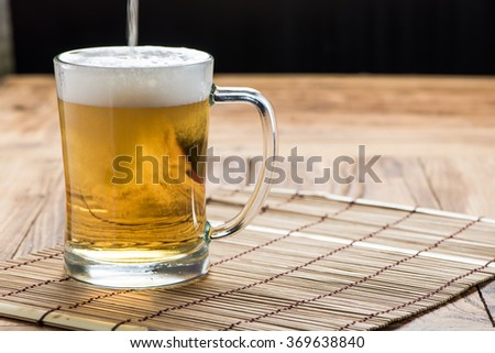 Beer pouring from top in bottle on wood table - stock photo