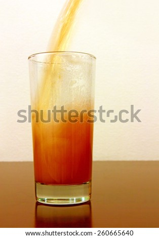 Beer pouring in glass taken closeup.Toned image. - stock photo
