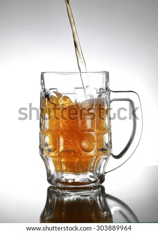 Beer pouring into a glass on light background