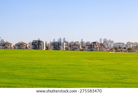 Beer Sheva suburb behind a green field, Israel - stock photo