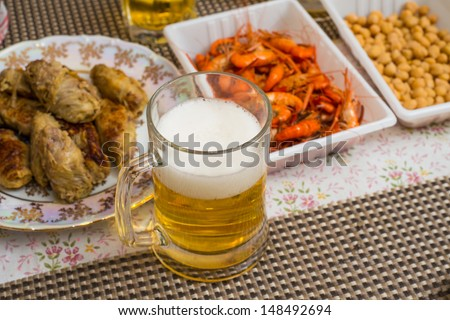 Beer, shrimp, pea, and other appetizers on a table  - stock photo