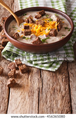 beer soup with sausage, cheddar cheese and croutons in a bowl close-up on the table. vertical - stock photo