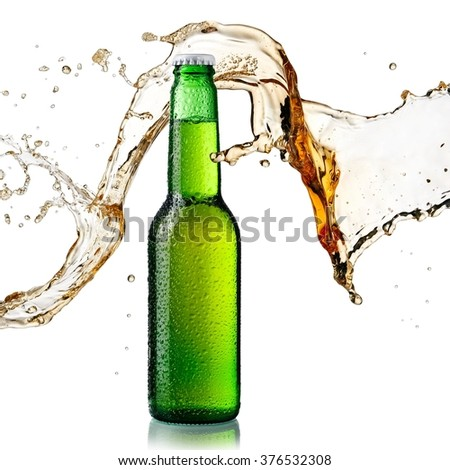 Beer splash over a green bottle with drops - stock photo