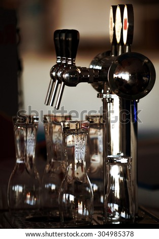 Beer tap and glasses ready to serve some pints - stock photo