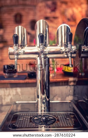 Beer taps at restaurant, bar, pub or bistro. Close-up details of beer draft taps in a row on barman counter in bar - stock photo