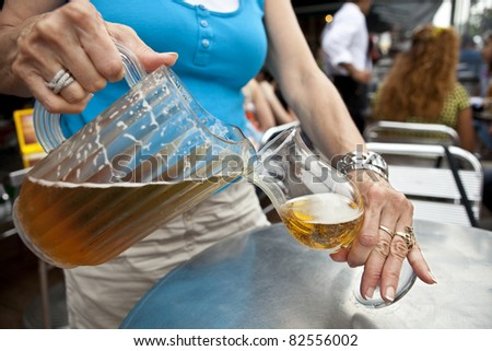 Beer Waitress Bar Maid pouring draught beer from a pitcher