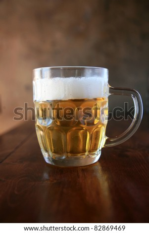 Beer. What more can I say?  Fresh been in a mug on a wooden table with a nice dark wall as a background in a restaurant on hot summer day. - stock photo
