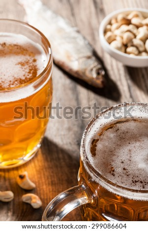 Beer with dried fish and snacks on wooden table